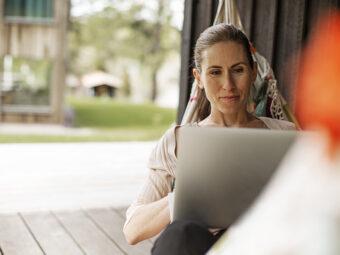 Kvinna i hängmatta med laptop.