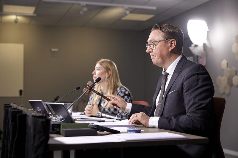 Man med ordförandeklubba och mikrofon närmast kameran, kvinna lite längre bort.