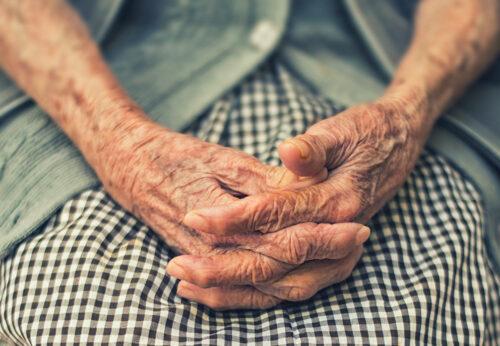 Äldre kvinnas knäppta händer i närbild