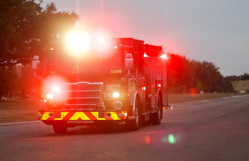branbil med lysande strålkastare på landsväg.