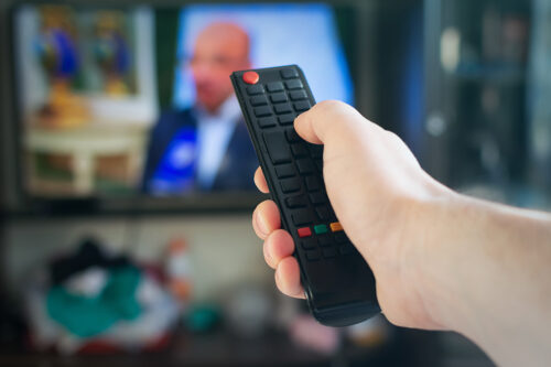Hand håller fjärrkontroll framför tv med person som talar.