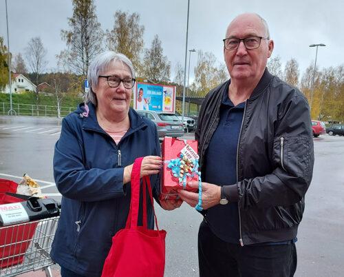 Äldre kvinna och man, halvbild, står och håller i en röd HRF-kasse och ett paket.